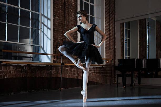 Ballerina performing passe devant in dance studio