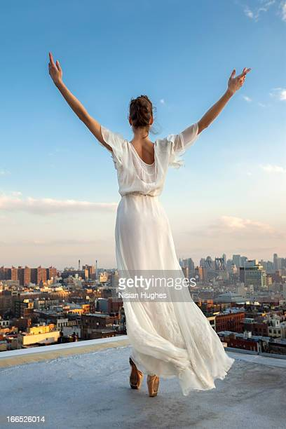 ballerina performing relevé on pointe on roof - robe longue photos et images de collection