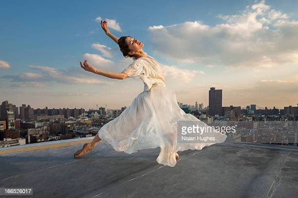 ballerina performing tombé, cambré back on roof - long dress stock pictures, royalty-free photos & images
