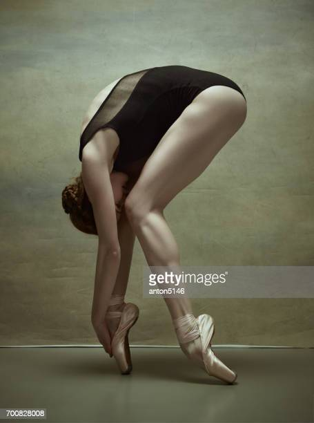 Ballerina posing in pointe shoes at gray pavilion
