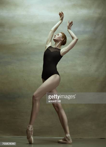 ballerina posing in pointe shoes at gray pavilion - action movie stock pictures, royalty-free photos & images