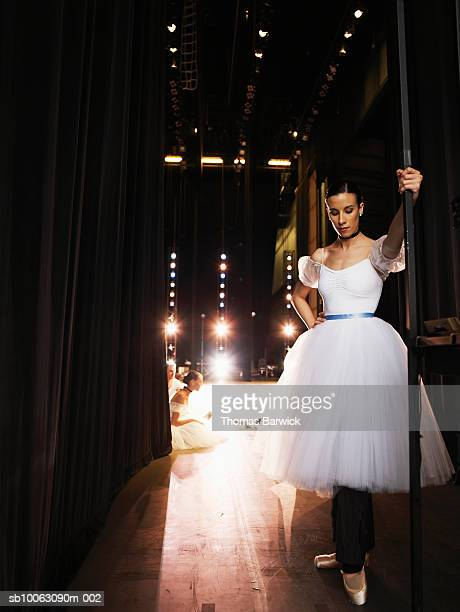 ballerina preparing in the wings, dancers stretching on stage in background - backstage stock pictures, royalty-free photos & images