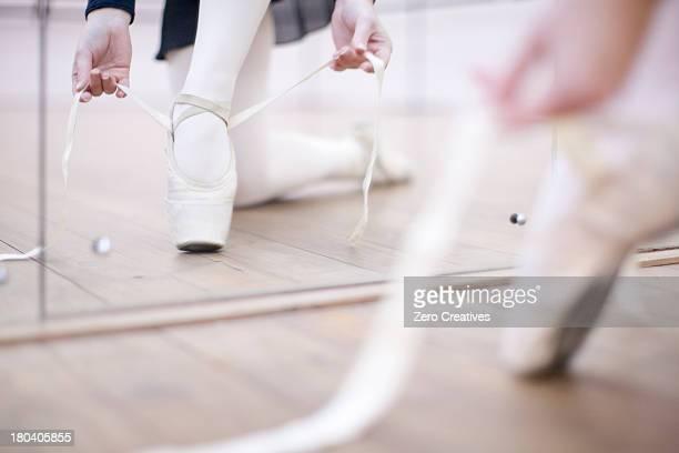 Ballerina putting on ballet slippers