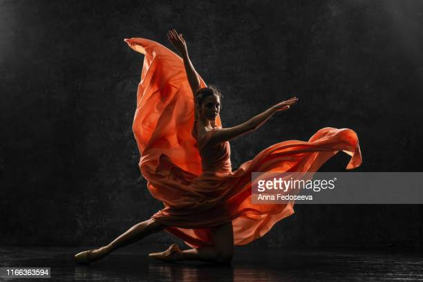 ballerina. silhouette photo of a young  ballet dancer dressed in a long peach dress, pointe shoes with ribbons. the girl performs an graceful dance movement. beautiful classic ballet. ballet studios. - performance stock pictures, royalty-free photos & images