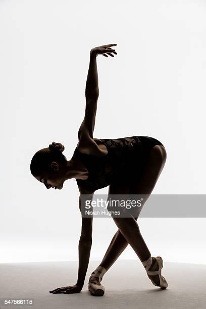 Ballerina silhouette stretching in studio