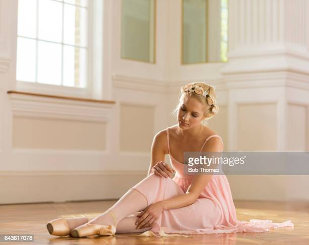 ballerina sitting on the floor tying her ballet shoes - satin dress stock pictures, royalty-free photos & images