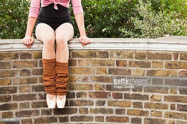 ballerina sitting on wall, low section - レッグウォーマー ストックフォトと画像