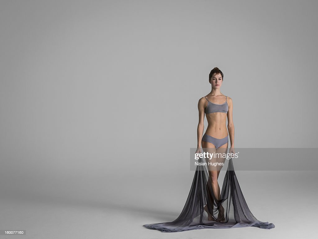 Beautiful ballet dancer standing looking at camera holding silk...