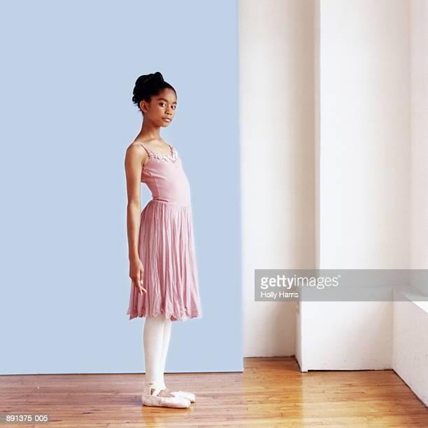 Ballerina (10-12) standing in dance studio, portrait