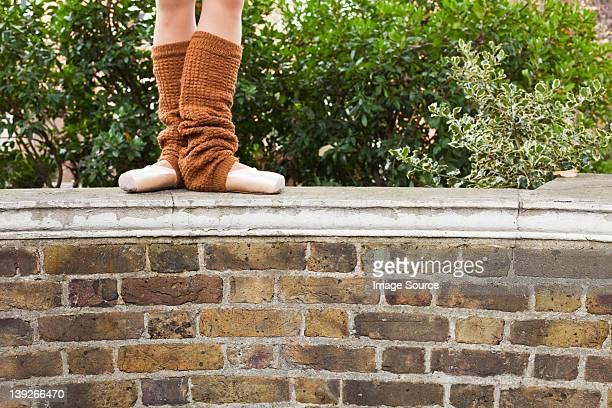 Ballerina standing on wall, low section