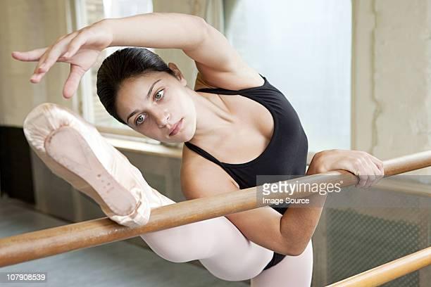 ballerina stretching at barre - タイツ ストックフォトと画像
