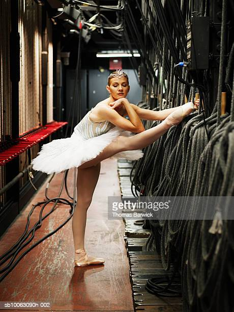 ballerina stretching leg backstage, chin on hand - performing arts event stock pictures, royalty-free photos & images
