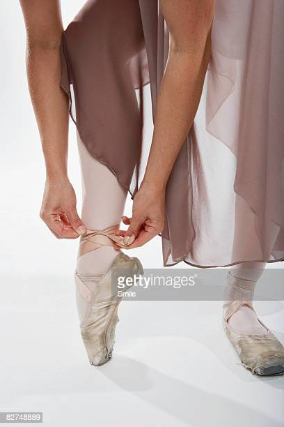Ballerina tying her point shoe, legs only