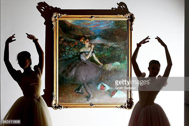 Ballerinas from The Australian Ballet are silhouetted as they pose next to one of Edgar Degas iconic ballet dancer paintings 'Dancer with Bouquets'...