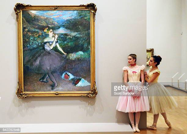 Ballerinas from The Australian Ballet look at one of Edgar Degas' iconic ballet dancer paintings 'Dancer with Bouquets' during the media preview for...