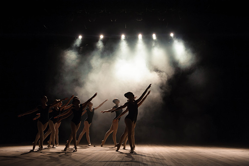 Ballet class on the stage of the theater with light and smoke. Children are engaged in classical exercise on stage. 1135143424