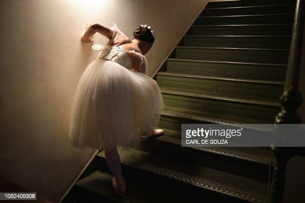 A ballet dancer adjusts her ballet slipper before performing on the second night of a Ballet production at the Municipal Theater in Rio de Janeiro...