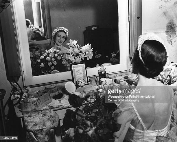 Ballet dancer, Alicia Markova, backstage in her dresssing room, surrounded by flowers, New York, ca.1950s.