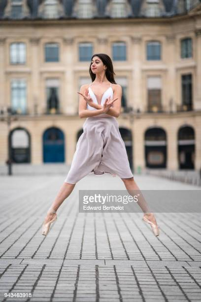 Ballet dancer Amanda Derhy performs a jump wears a white leotard ballet shoes and a light purple skirt at Place Vendome on March 25 2018 in Paris...