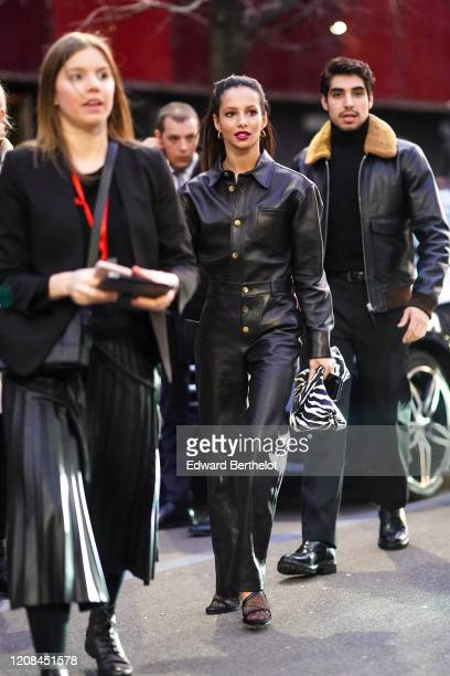 Ballet dancer and actress Francesca Hayward wears earrings a black leather shirt black leather pants a black and white zebra pattern clutch black...