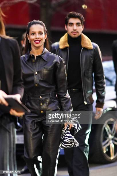 Ballet dancer and actress Francesca Hayward wears earrings a black leather shirt black leather pants a black and white zebra pattern clutch outside...
