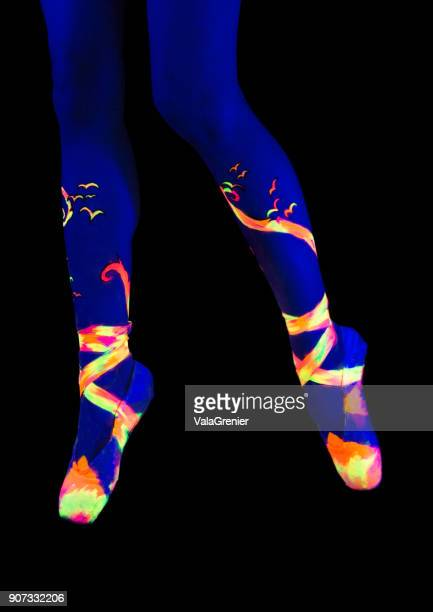 Ballet dancer, feet in point shoes and ankles in black light body paint.