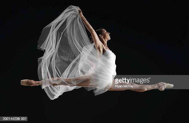 Ballet dancer in mid air splits, arms extended, side view