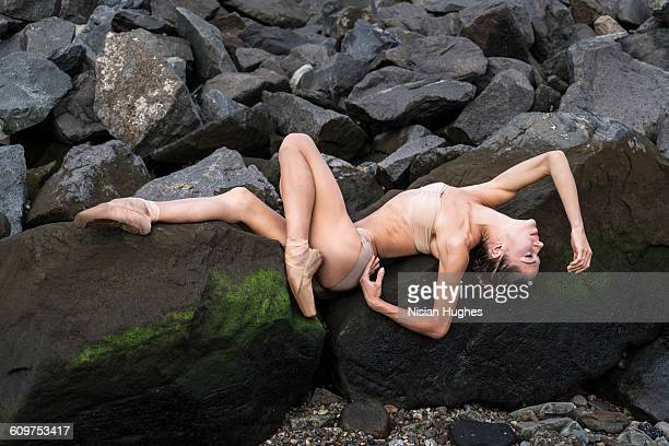 Ballet dancer laying down over moss covered rocks