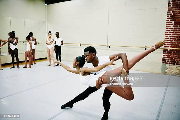 Ballet dancer lifting partner during rehearsal