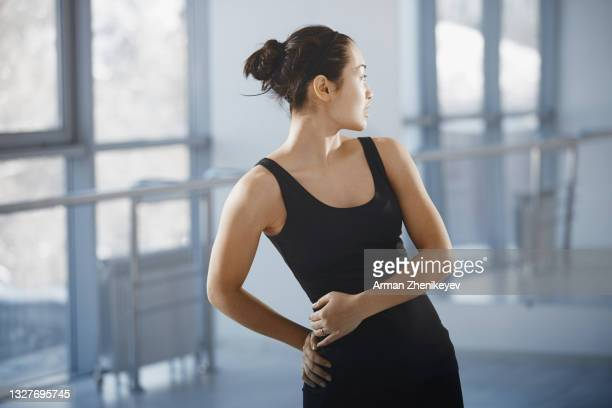 ballet dancer looking over the shoulder in a mirror at the dance studio - looking over shoulder ストックフォトと画像