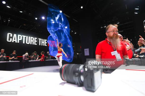 A ballet dancer performs at the Canon stand at the Photokina trade fair in Cologne western Germany on September 27 2018 The fair for the photographic...