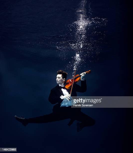 ballet dancer playing violin underwater