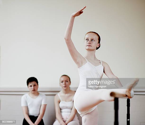 Ballet dancer practising move as others observe