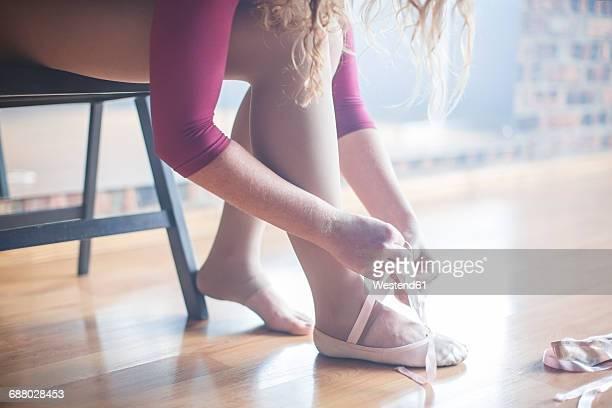 Ballet dancer putting shoes on