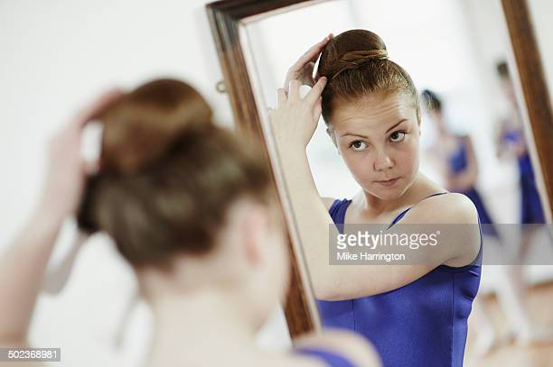 Ballet dancer tying hair in bun in mirror.