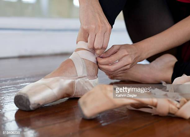 ballet dancer tying her pointe shoes