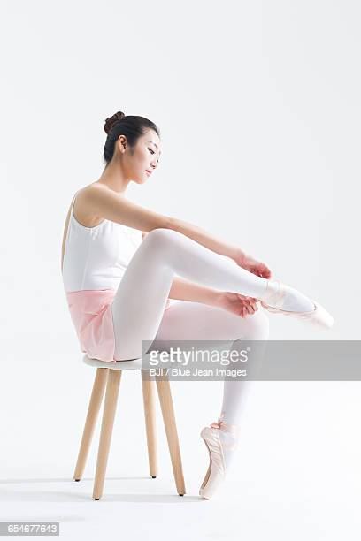 Ballet dancer tying up pointe shoes