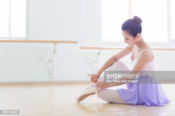 ballet dancer tying up pointe shoes - ballettstudio stock-fotos und bilder