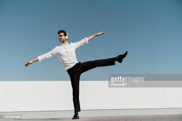 ballet dancer with headphones practising on roof terrace - 白いシャツ ストックフォトと画像