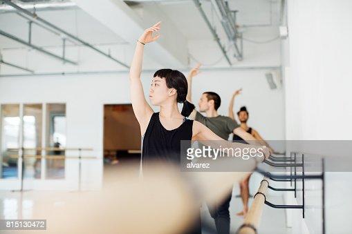 Ballet dancers practicing at barre in dance studio