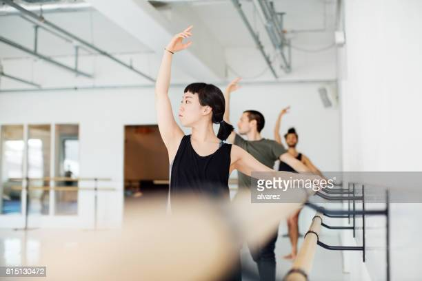 ballet dancers practicing at barre in dance studio - barre stock photos and pictures