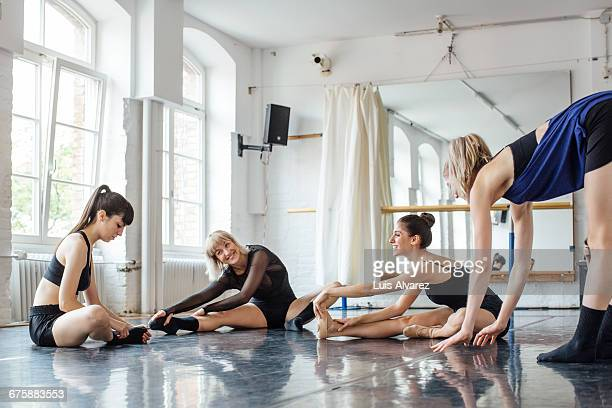 Ballet dancers stretching legs at studio