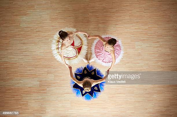 Ballet girls posing hand in hand, top view