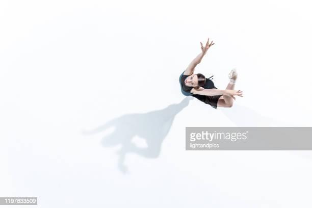 ballet in white studio - アラベスクポジション ストックフォトと画像