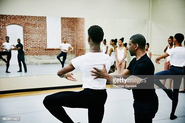 Ballet instructor adjusting students form