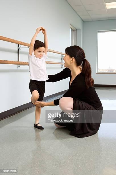 Ballet instructor correcting boy's position