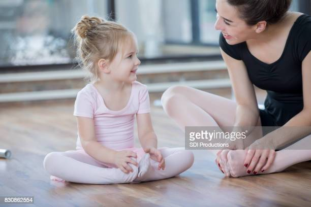 ballet instructor guides young student in floor stretches - little girls dressed up wearing pantyhose stock photos and pictures