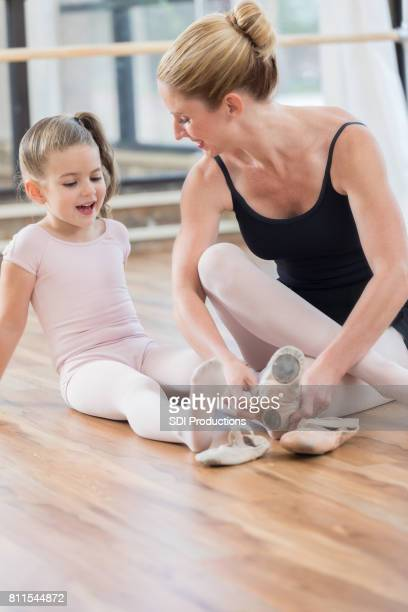 ballet instructor helps student with ballet shoes - little girls dressed up wearing pantyhose stock photos and pictures
