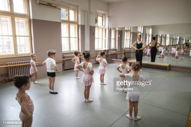 ballet instructor showing basic steps to a cute group of little girls - dance studio stock pictures, royalty-free photos & images