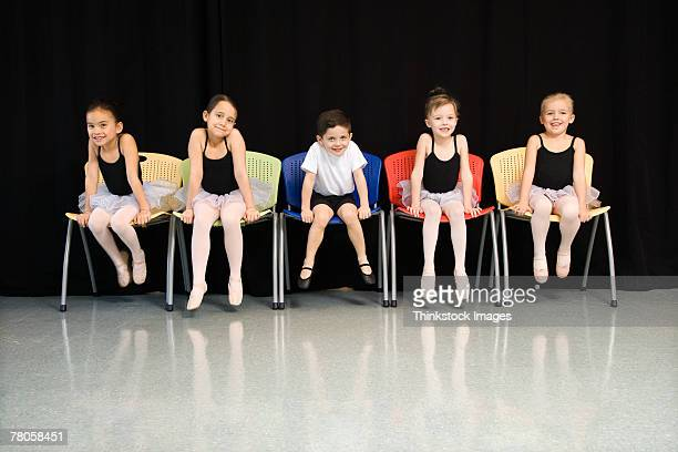 Ballet students sitting in a row